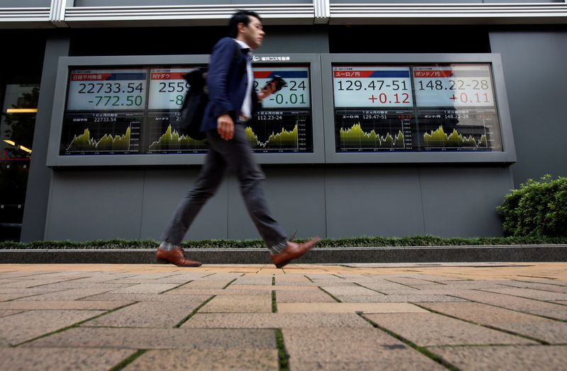 © Reuters. A passerby walks past an electronic boards Japan's Nikkei average, the Dow Jones Industrial Average and foreign exchange rates outside a brokerage in Tokyo