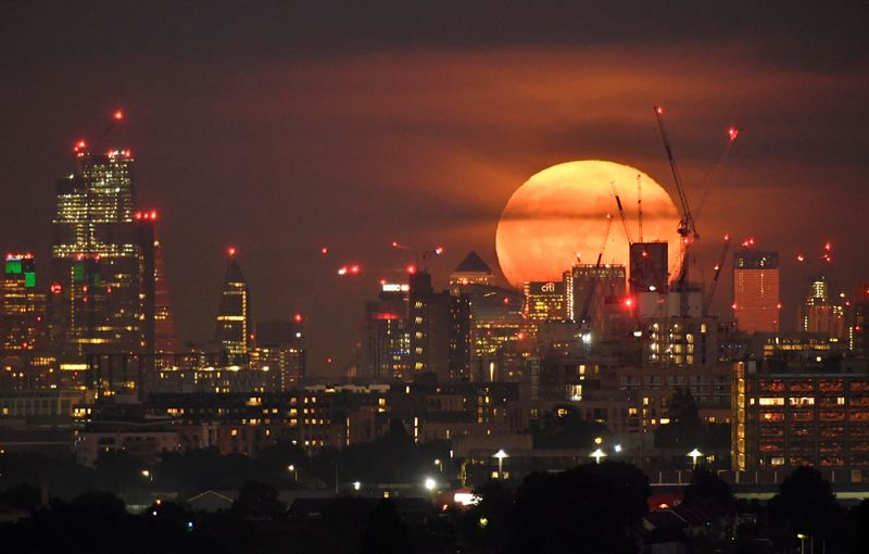 © Reuters. The full moon is seen rising behind skyscrapers at Canary Wharf and the London skyline, London, Britain