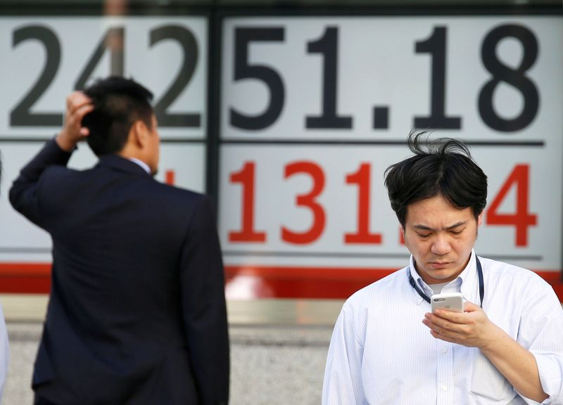 © Reuters. Men stand in front of an electronic board showing Japan's Nikkei average outside a brokerage in Tokyo