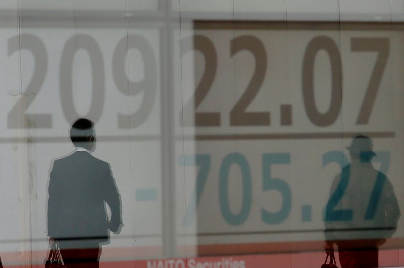 © Reuters. FILE PHOTO: Men are reflected on an electronic board showing the Nikkei stock index outside a brokerage in Tokyo