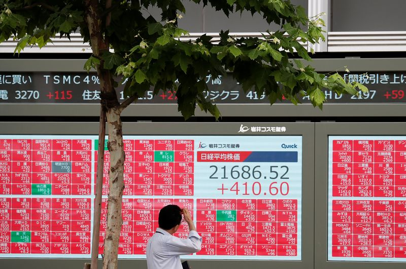 © Reuters. FILE PHOTO: A man looks at a stock quotation board outside a brokerage in Tokyo