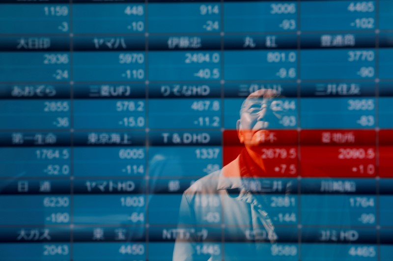 © Reuters. A man is reflected on a board showing stock prices outside a brokerage in Tokyo