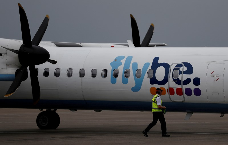 © Reuters. FILE PHOTO: An airport worker examines a flybe aircraft before it takes off from Liverpool John Lennon Airport in Liverpool northern England.