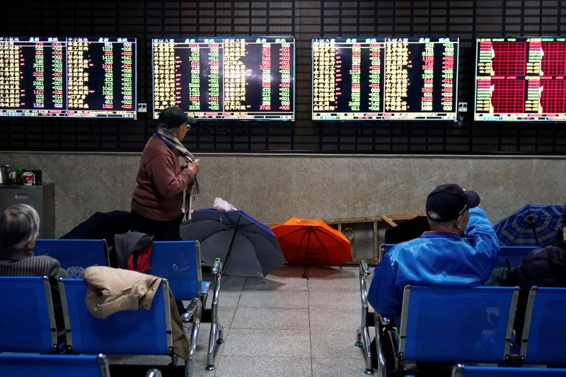 © Reuters. Investors look at screens showing stock information at a brokerage house in Shanghai