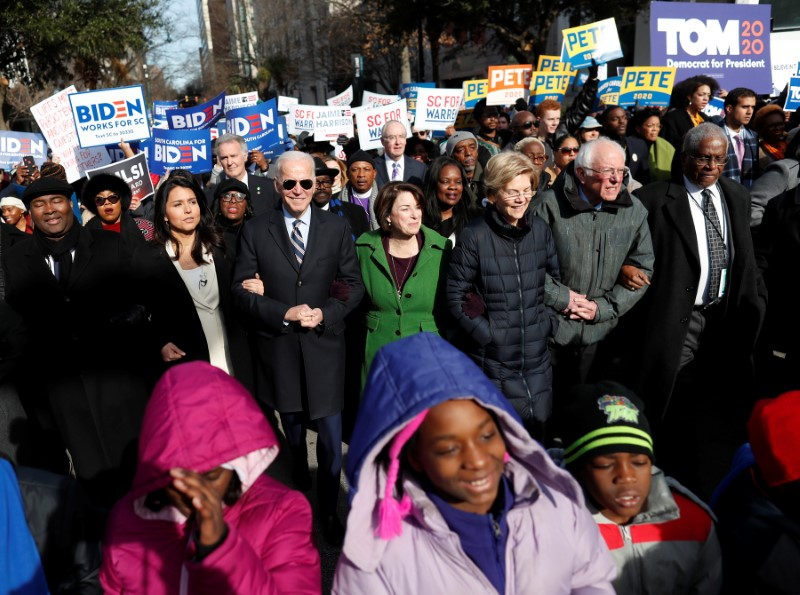 © Reuters. Seven of the democratic U.S. 2020 presidential candidates walk arm-in-arm with local African-American leaders during the Martin Luther King Jr. (MLK) Day Parade in Columbia