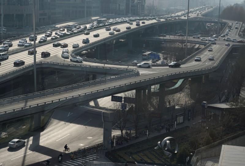 © Reuters. Un hombre pedalea bajo el puente Guomao en Beijing