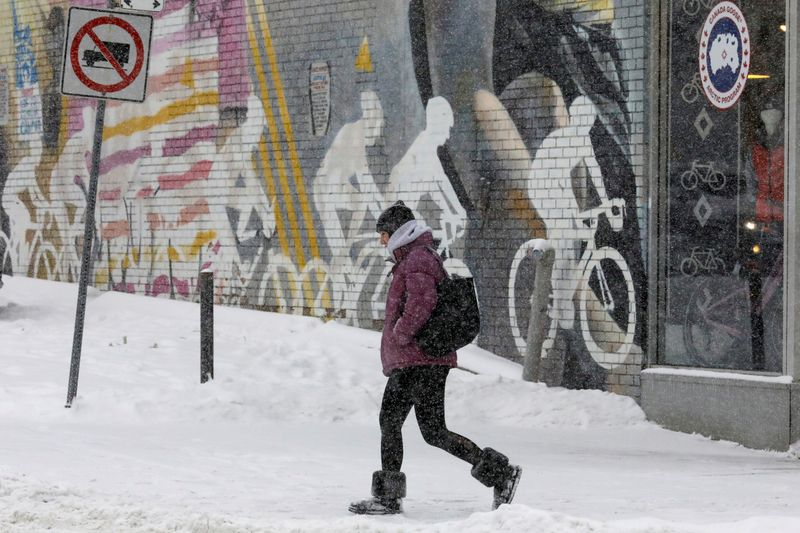 © Reuters. FILE PHOTO: A woman passes a sporting goods store during a snow storm in Toronto