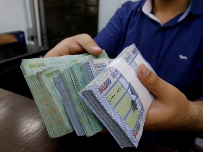 © Reuters. FILE PHOTO: A money exchange vendor displays Lebanese pound banknotes at his shop in Beirut