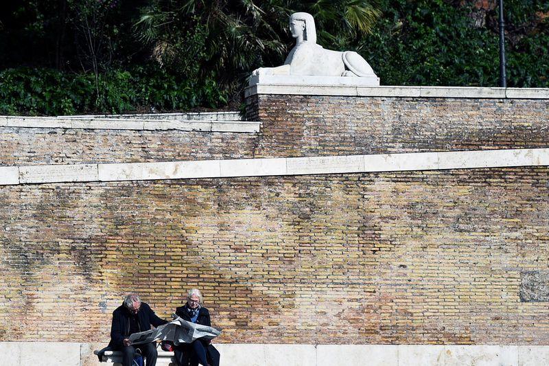© Reuters. FOTO DE ARCHIVO: La gente lee el periódico en la Piazza del Popolo en Roma