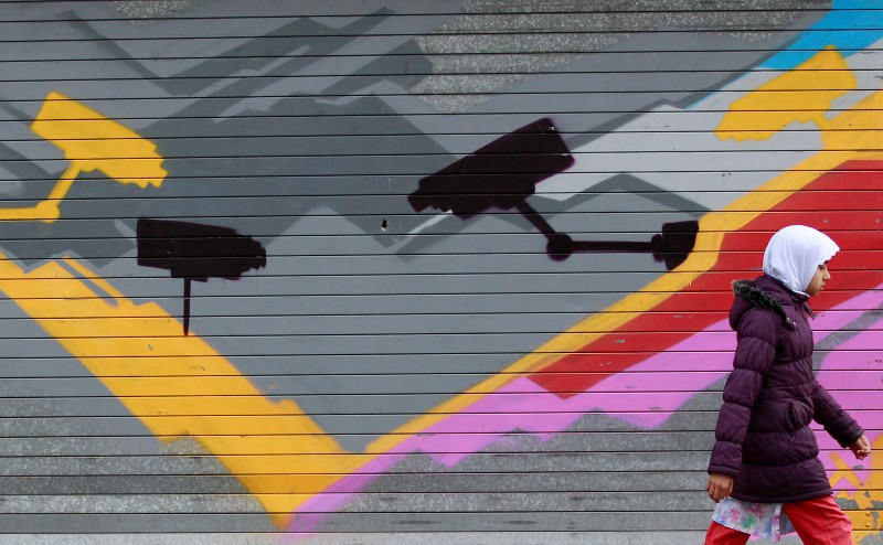 © Reuters. FILE PHOTO: A girl walks past graffiti showing CCTV cameras in the Sparkbrook area of Birmingham