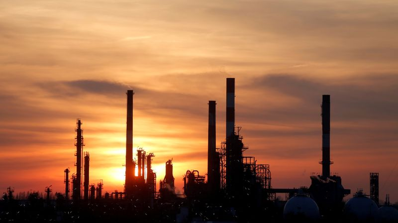 © Reuters. FILE PHOTO: The sun sets behind the chimneys of the Total Grandpuits oil refinery southeast of Paris