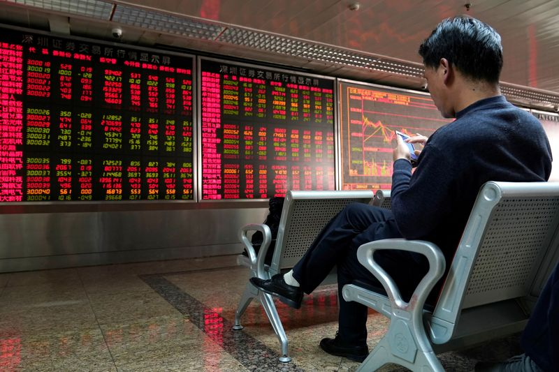 © Reuters. An investor uses his mobile phone in front of a stock quotation board at a brokerage office in Beijing
