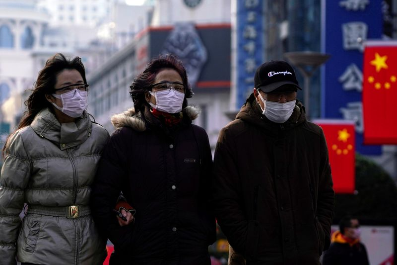© Reuters. People wearing protective masks walk at the Nanjing Road in Shanghai