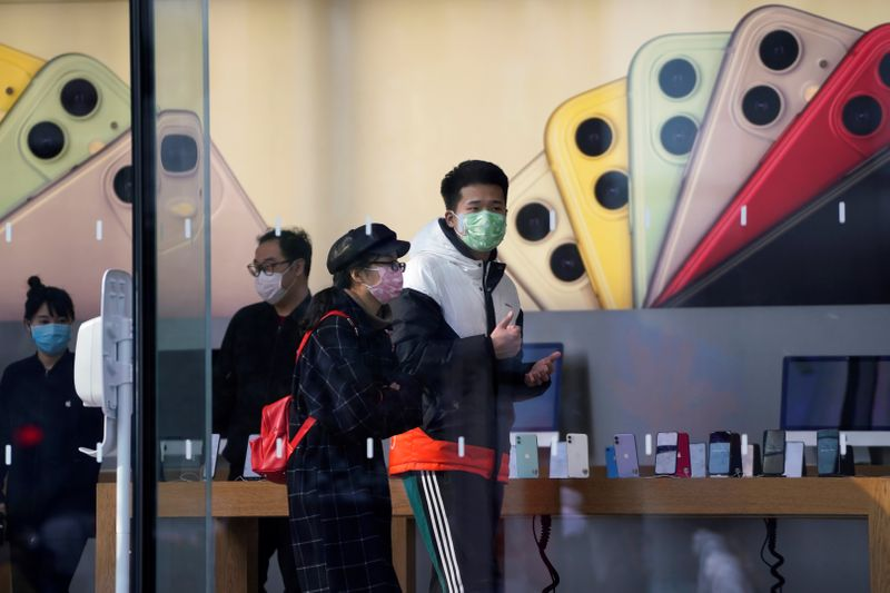© Reuters. People wearing protective masks are seen in an Apple Store, as China is hit by an outbreak of the new coronavirus, in Shanghai