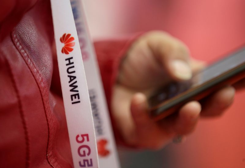 © Reuters. FILE PHOTO: An attendee wears a badge strip with the logo of Huawei and a sign for 5G at the World 5G Exhibition in Beijing