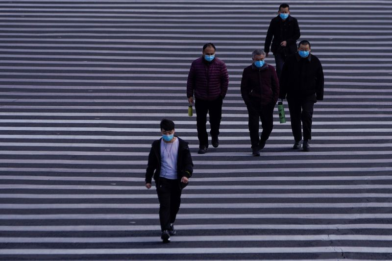 © Reuters. People wearing masks are seen at Lujiazui financial district in Pudong, Shanghai