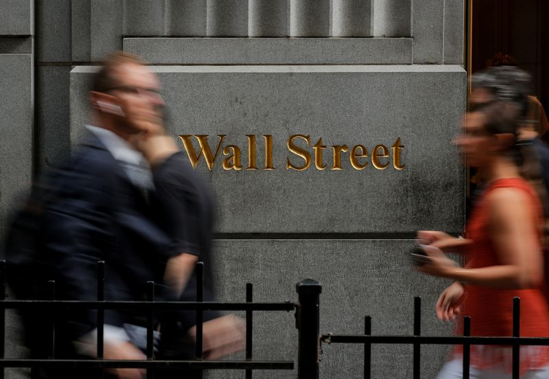 © Reuters. People walk on Wall St. outside the NYSE in New York