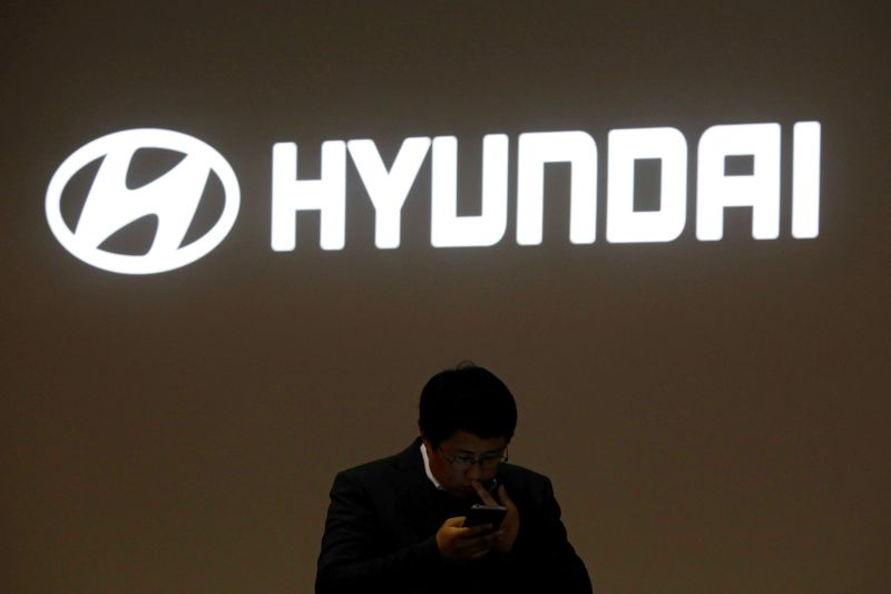 © Reuters. FILE PHOTO: A man walks past the logo of Hyundai Motor during the 2019 Seoul Motor Show in Goyang