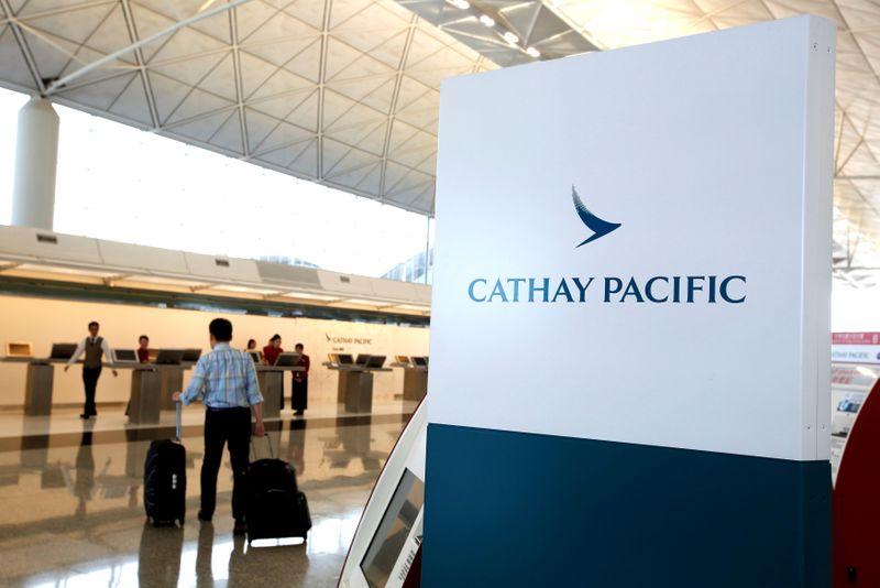 © Reuters. A passenger walks to the First Class counter of Cathay Pacific Airways at Hong Kong Airport in Hong Kong