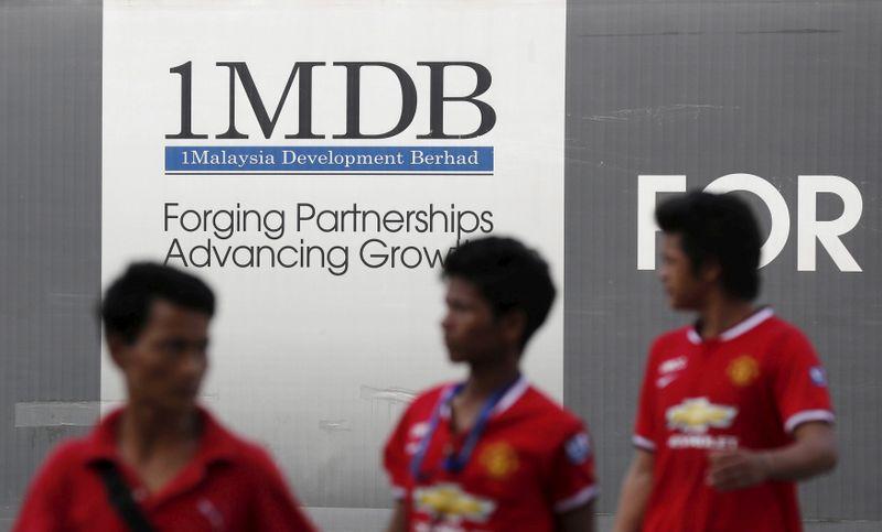 © Reuters. Men walk past a 1 Malaysia Development Berhad (1MDB) billboard at the fund's flagship Tun Razak Exchange development in Kuala Lumpur