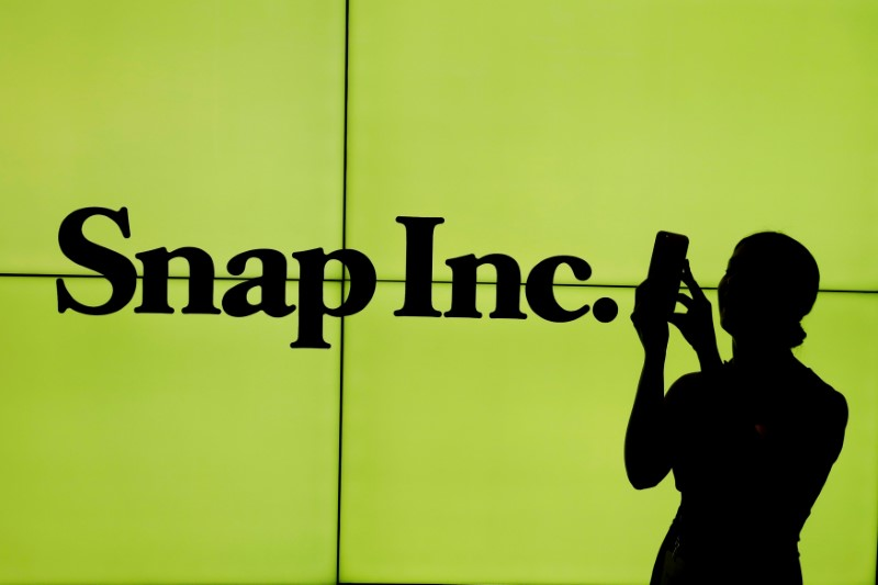 © Reuters. FILE PHOTO: A woman stands in front of the logo of Snap Inc. on the floor of the New York Stock Exchange in New York City