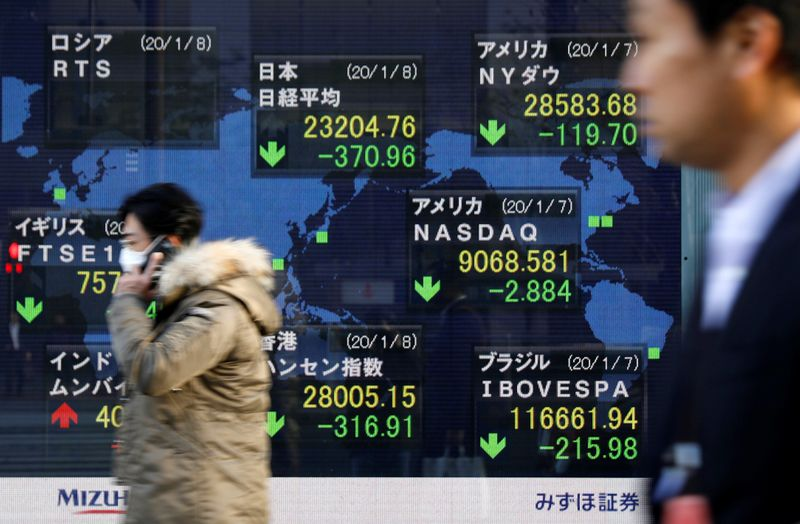 © Reuters. People walk past an electronic display showing world markets indices outside a brokerage in Tokyo