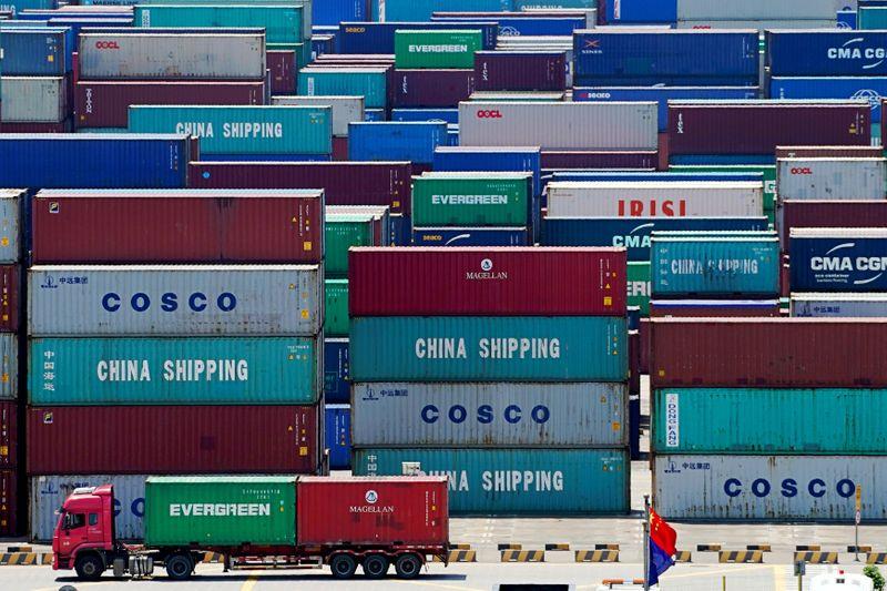 © Reuters. FOTO DE ARCHIVO: Se ven camiones que transportan contenedores cerca de una bandera china en el puerto de aguas profundas de Yangshan en Shanghai
