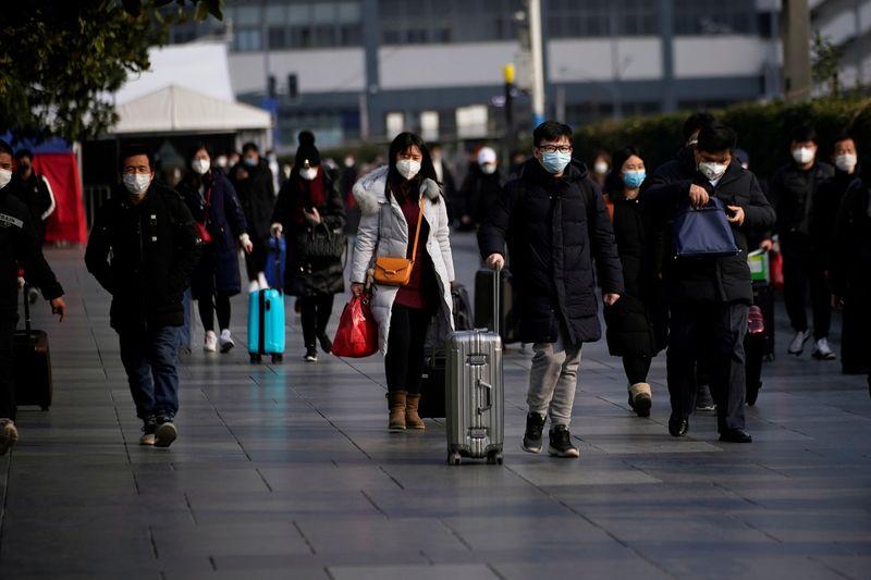 © Reuters. Pasajeros con máscaras caminan en la estación de tren de Shanghai