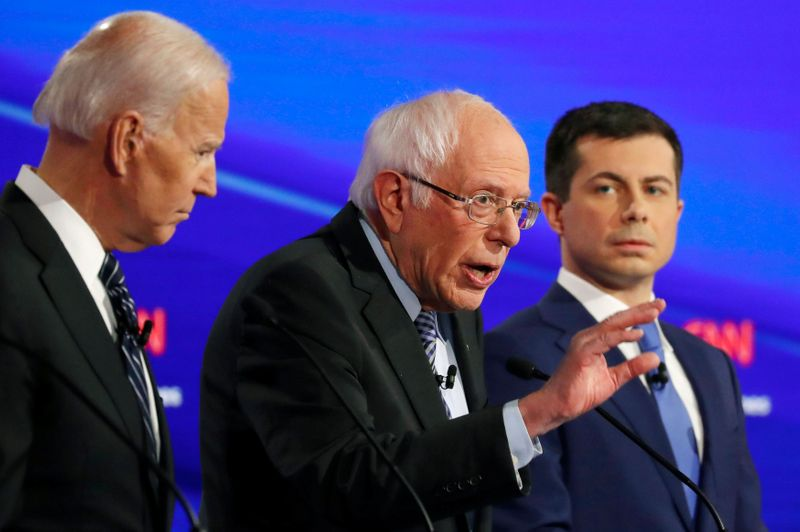 © Reuters. FILE PHOTO: Democratic 2020 U.S. presidential candidates former Vice President Joe Biden listens to Senator Bernie Sanders as former South Bend Mayor Pete Buttigieg looks on in the seventh Democratic 2020 presidential debate at Drake University in Des Moi
