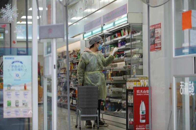 © Reuters. Worker is seen inside a convenience store following an outbreak of the novel coronavirus in Wuhan
