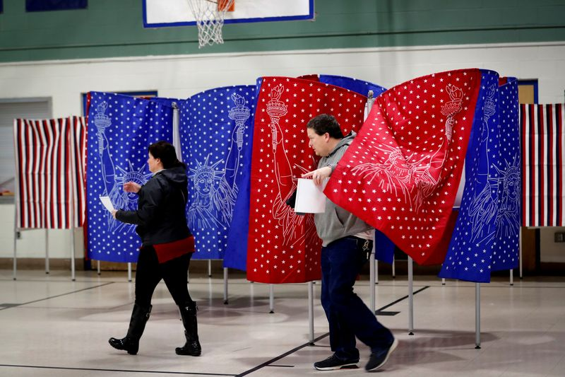 © Reuters. Voters carry ballots from voting booths while voting in the New Hampshire U.S. presidential primary election in Manchester