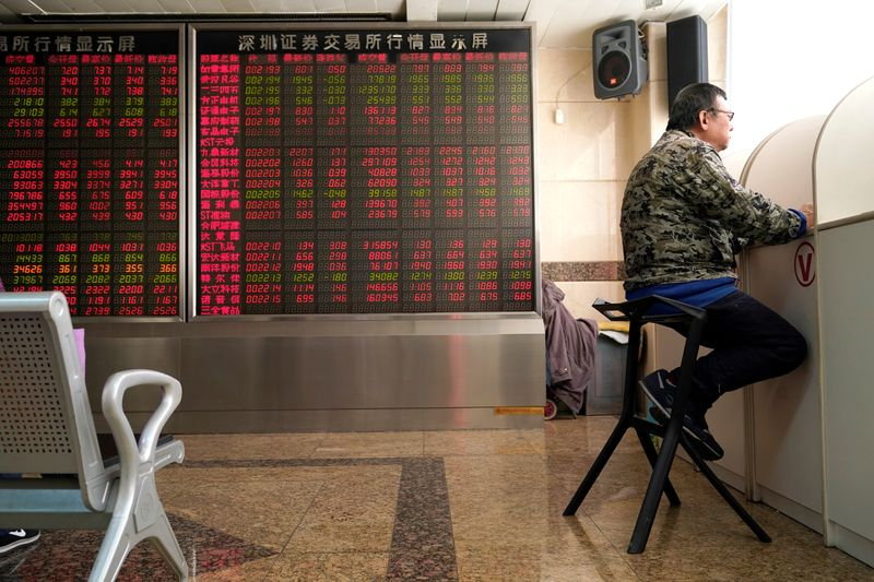 © Reuters. An investor sits next to a stock quotation board at a brokerage office in Beijing