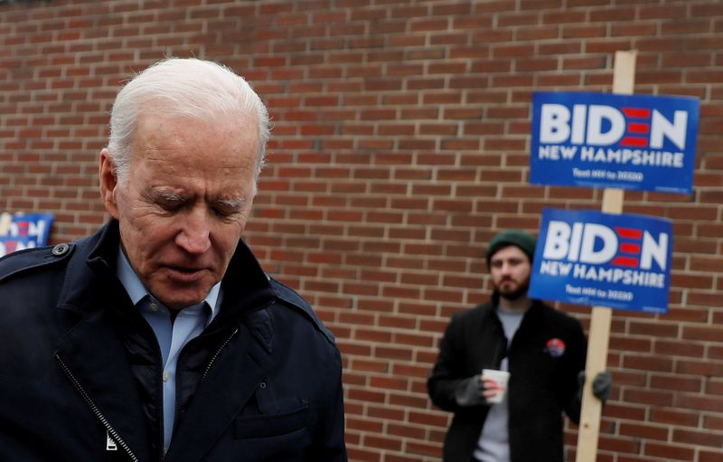 © Reuters. FILE PHOTO: A supporter for Democratic 2020 U.S. presidential candidate and former Vice President Joe Biden holds a sign as Biden leaves a polling station after a visit, on the day of New Hampshire's first-in-the-nation primary in Manchester, New Ham