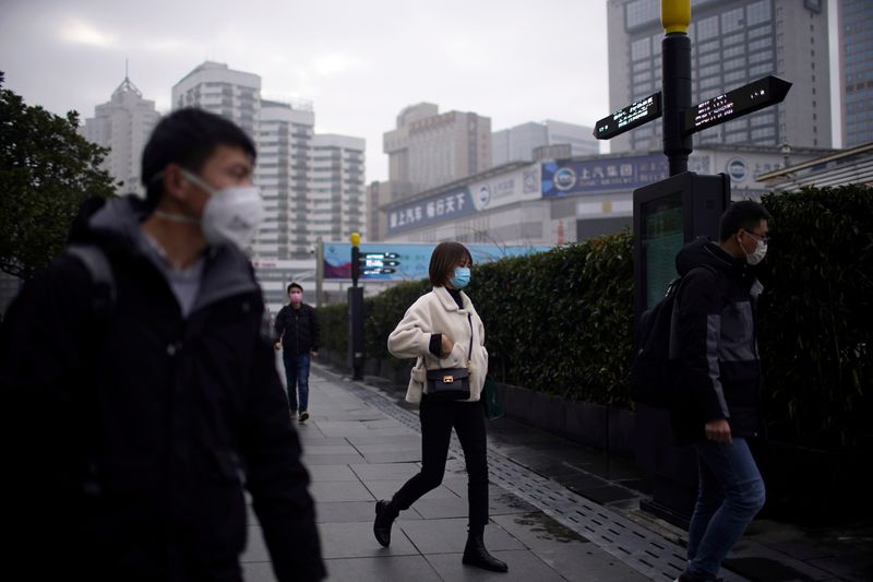 © Reuters. People wearing masks are seen at a square in Shanghai
