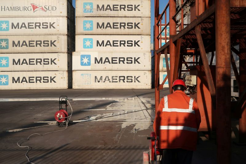 © Reuters. Worker is seen next to Maersk shipping containers at a logistics center nearTianjin por