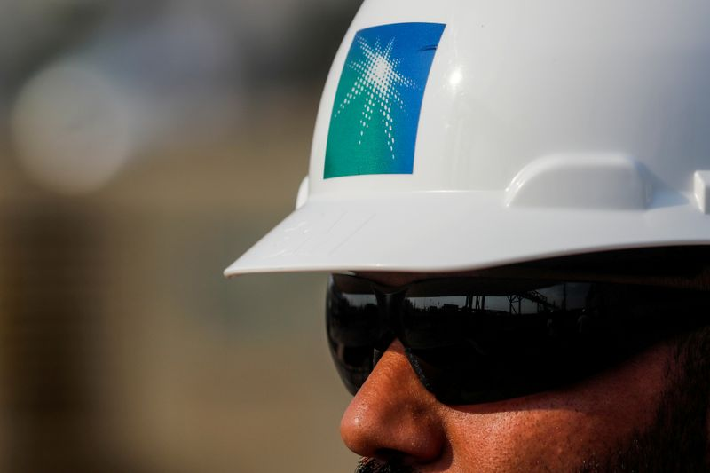 © Reuters. FILE PHOTO: An employee in a Saudi Aramco branded helmet