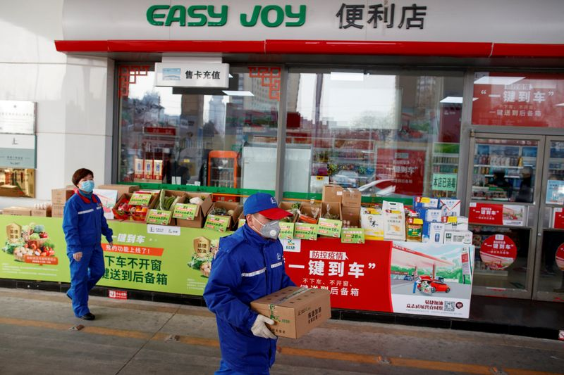 © Reuters. FILE PHOTO: A pump attendant carries a box of groceriees into a car at a Sinopec gas station in Beijing where customers can buy supplies while they refuel