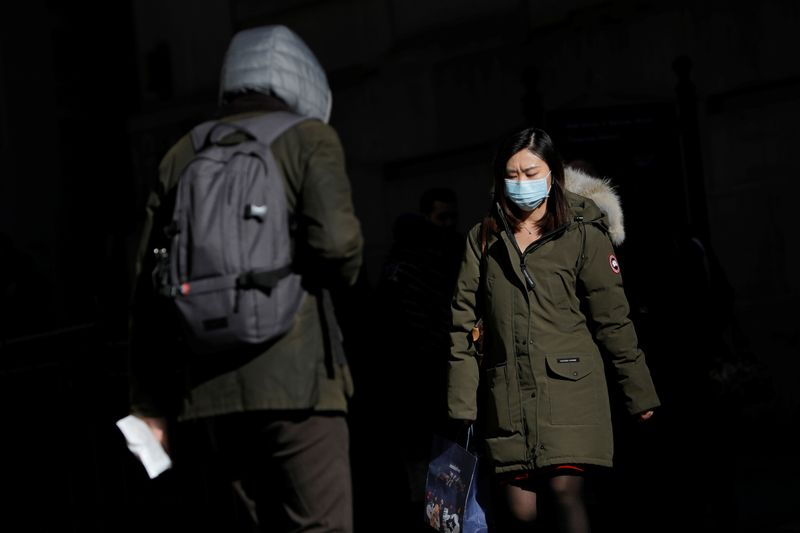 © Reuters. A woman in a face mask walks in the downtown area of Manhattan, New York City, after further cases of coronavirus were confirmed in New York