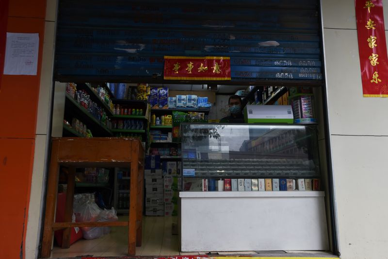 © Reuters. Man wearing a face mask stands inside a shop with the roller shutter half closed, in Wuhan, the epicentre of the novel coronavirus outbreak