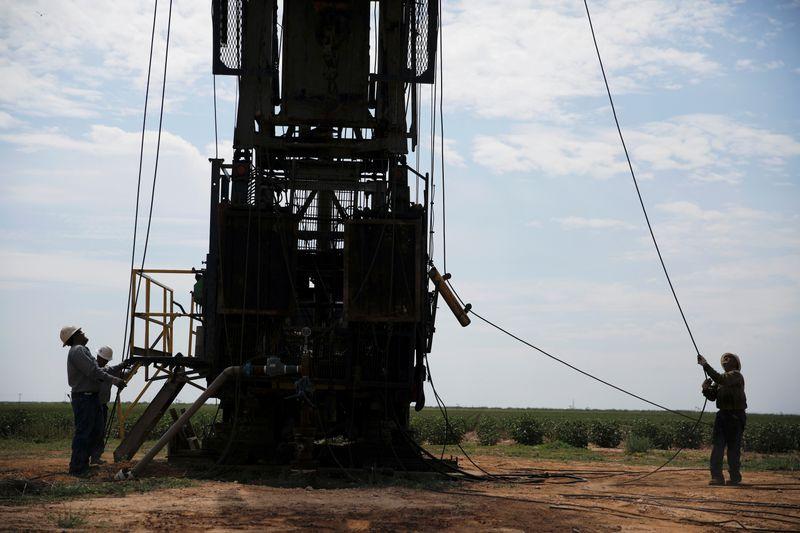 © Reuters. FILE PHOTO: Oil field workers prepare a swabbing rig in a cotton field in Seminole