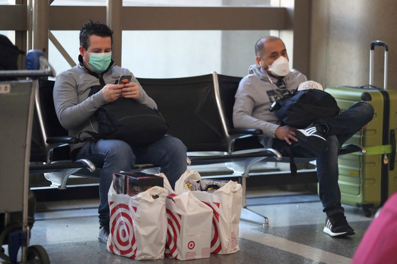 © Reuters. FILE PHOTO: People wear masks at the international terminal at LAX airport in Los Angeles