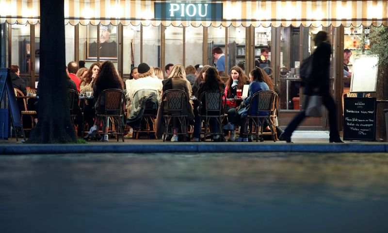 © Reuters. People sit in a outside restaurant, as France's Prime Minister announced to close most all non-indispensable locations, notably cafes, restaurants, cinemas, nightclubs and shops from midnight on Saturday, In Paris