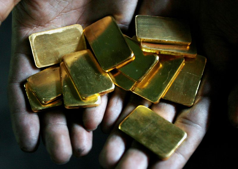 © Reuters. FILE PHOTO: A worker shows gold biscuits at a precious metals refinery in Mumbai