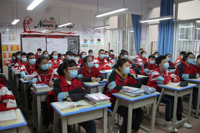© Reuters. Junior high students wearing face masks attend a class on their first day of returning to school following an outbreak of the novel coronavirus, in Guiyang, Guizhou
