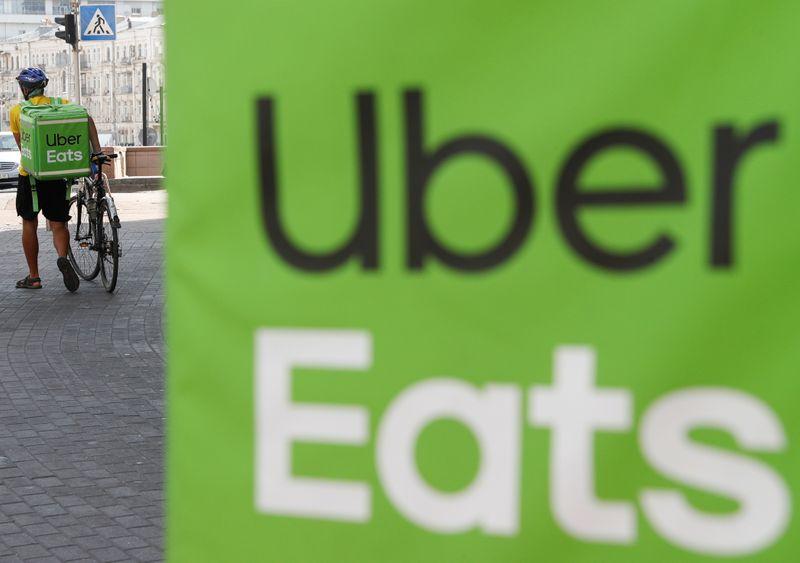 © Reuters. An Uber Eats courier walks in Kiev