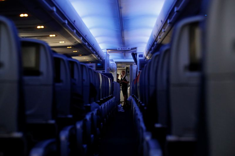 © Reuters. Flight attendants stand at the end of rows of empty seats aboard a Delta flight from New York to San Francisco