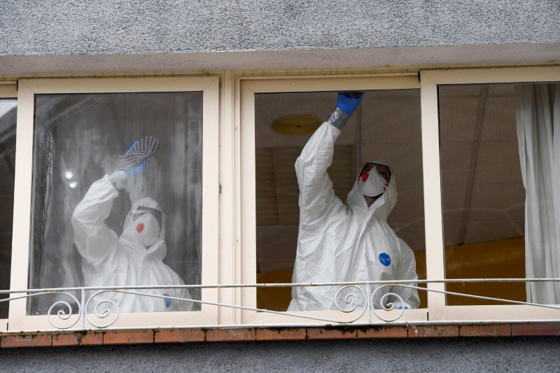 © Reuters. FILE PHOTO: FILE PHOTO: Sanitary workers clean the nursing home where a woman died and several residents and care providers have been diagnosed with coronavirus disease (COVID-19) in Grado