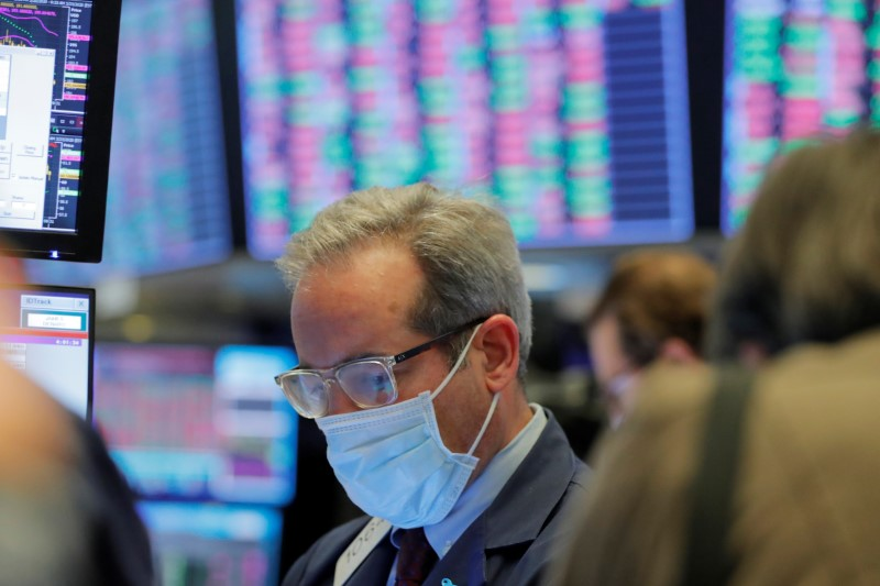 © Reuters. A trader wears a mask as he works on the floor of the New York Stock Exchange (NYSE) as the building prepares to close indefinitely due to the coronavirus disease (COVID-19) outbreak in New York