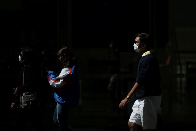 © Reuters. FILE PHOTO: Pedestrians wear protective face masks amidst fears of the coronavirus disease (COVID-19) in Sydney