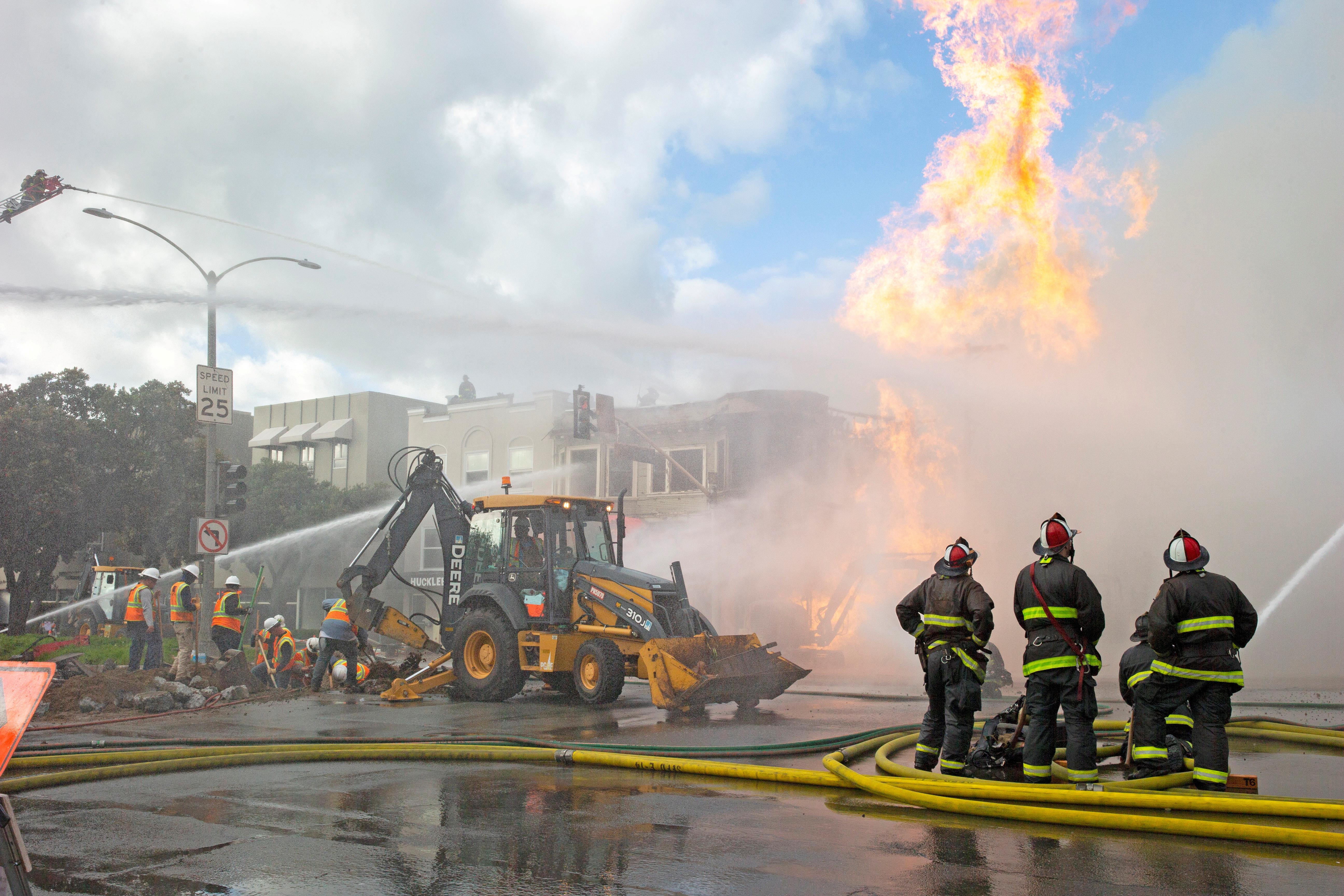 © Reuters. FILE PHOTO: Firefighters battle a fire following an explosion at Geary Boulevard and Parker Avenue as PG&E officials dig up the ground to reach the pipe in San Francisco